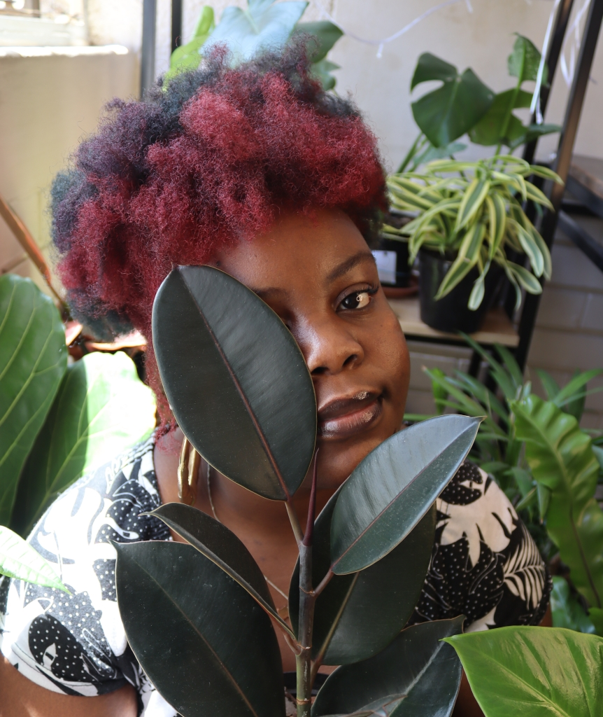 Black woman with a multicolor afro and is surrounded by plants